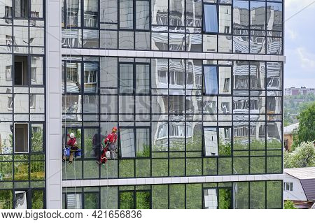 Yekaterinburg, Russia- May 10, 2020: Two Industrial Climbers From The Cleaning Service Wash The Glas