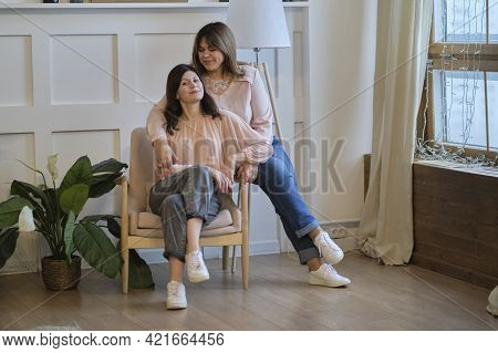 Beautiful Senior Mom And Her Adult Daughter Are Hugging And Smiling While Sitting On Couch At Home