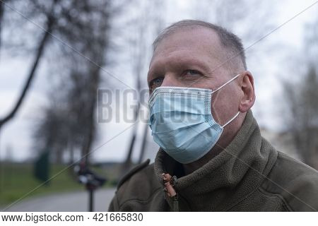 Mature Senior Man Alone In Park In Blue Face Mask.