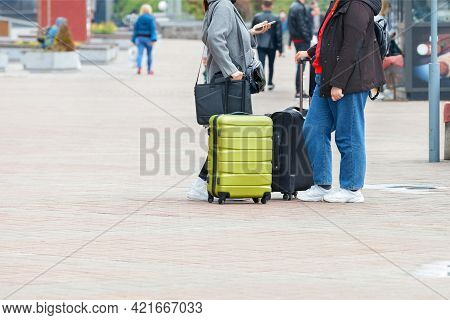 A Couple Of Travelers With Luggage, Waiting On The Sidewalk, Discuss Their Next Steps, Checking Thei
