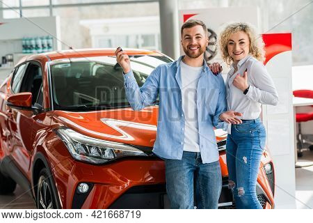 Happy Couple In Car Dealership On The Background Of Their New Car