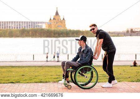 Help For People With Physical Disabilities. Man Drive Wheelchair And Help His Friend. Social Service