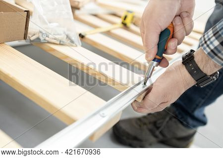 Close Up Of A Hands Assembling A Bed Frame Using A Screwdriver. Furniture Mounting Concept