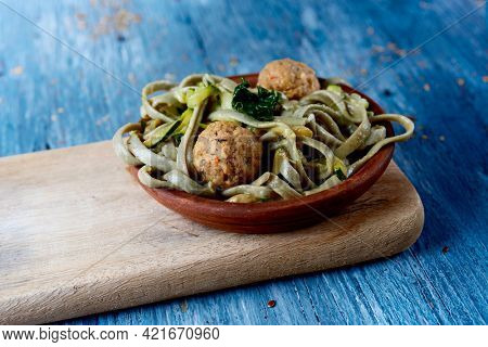closeup of an earthenware plate with some spelt tagliatelle with vegan meatballs, kale and zucchini, on a rustic blue wooden table
