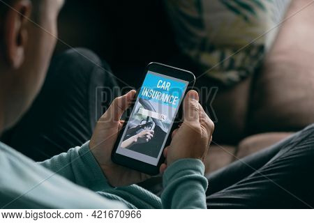closeup of a young caucasian man, sitting on a brown sofa in his living room, looking for car insurance online on his smartphone, with a simulated search engine