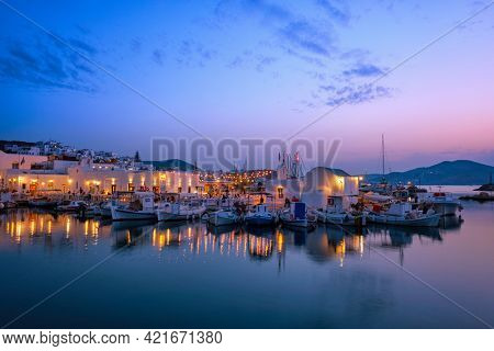 Picturesque view of Naousa town in famous tourist attraction Paros island, Greece with traditional whitewashed houses and moored fishing boats and seaside restaurants and cafe illuminated in night