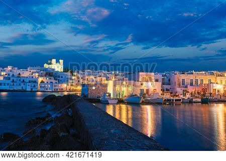 Picturesque view of Naousa town in famous tourist attraction Paros island, Greece with traditional whitewashed houses and moored fishing boats illuminated in the evening