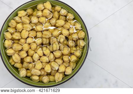 Chickpeas Soaked In Water, In Bowl, On Marble Table. Concept Of Healthy Eating, Veganism, Vegetarian