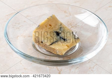 Spoiled Dried Cheese Scrap. Small Piece Of Dor Blue Cheese Has Dried On A Plate On The Table. Food S