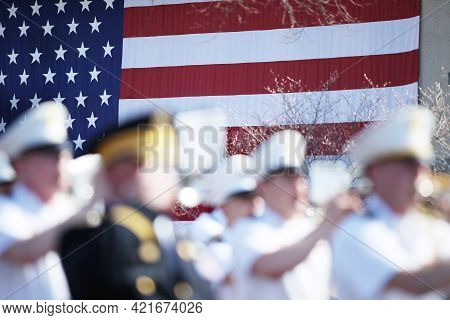 Out Of Focus Marching Band With The Us Flag In The Background.