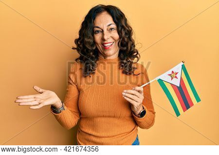Middle age hispanic woman holding zimbabwe flag celebrating achievement with happy smile and winner expression with raised hand