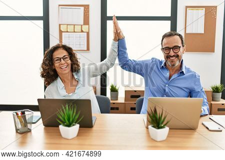 Two middle age business workers smiling happy and high five at the office.