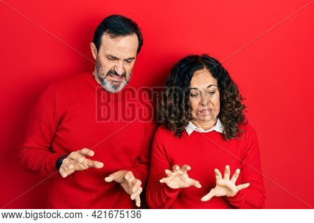 Middle age couple of hispanic woman and man hugging and standing together disgusted expression, displeased and fearful doing disgust face because aversion reaction.
