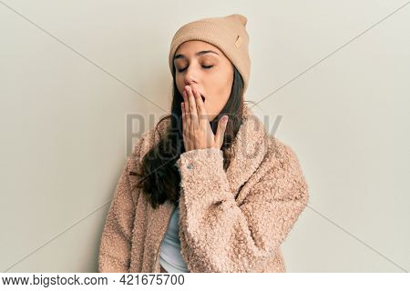 Young hispanic woman wearing wool sweater and winter hat bored yawning tired covering mouth with hand. restless and sleepiness.