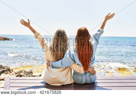 Young lesbian couple of two women in love at the beach. Beautiful women together at the beach in a romantic relationship sitting on a bench