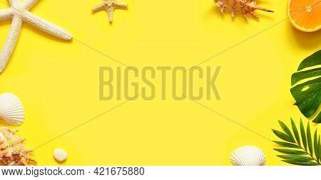 Summer Background. Palm Leaf, Orange, Starfish And Seashell On Yellow Background. Travel.