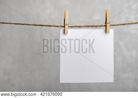 One Blank Square Note Paper Card Hanging With Wooden Clip Or Clothespin On Rope String Peg. Copy Spa
