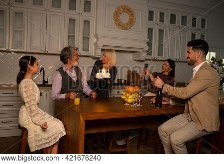 Making Wish. Big Happy Multigenerational Family Celebrating Birthday Of Grandfather Sitting At Table