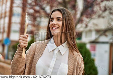 Young hispanic girl smiling happy holding paintbrushes at the city.