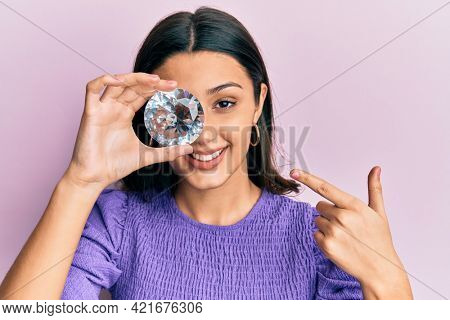 Young hispanic woman holding brilliant diamond stone smiling happy pointing with hand and finger