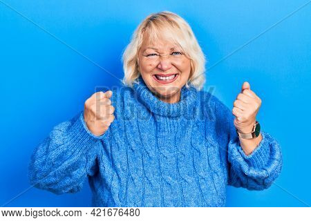 Middle age blonde woman wearing casual clothes angry and mad raising fists frustrated and furious while shouting with anger. rage and aggressive concept.