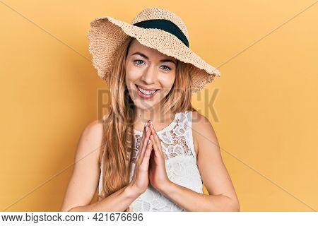 Young caucasian woman wearing summer hat praying with hands together asking for forgiveness smiling confident.