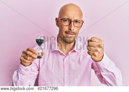 Bald man with beard holding sand clock annoyed and frustrated shouting with anger, yelling crazy with anger and hand raised