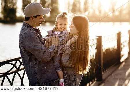 Young Beautiful Family Walks By The River In The Park With Their Little Daughter At Sunset. Dad And