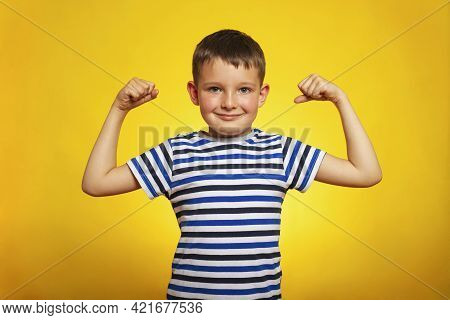 A Child Boy Showing His Hand Biceps Muscles Strength On Yellow Background. Smart Kid Showing His Arm