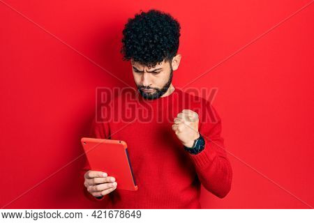 Young arab man with beard using touchpad device annoyed and frustrated shouting with anger, yelling crazy with anger and hand raised
