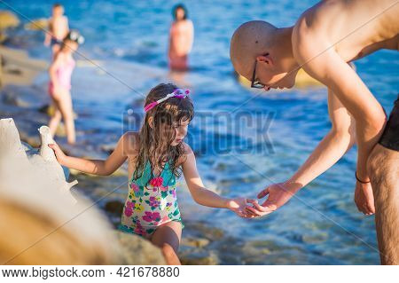 Little Girl With Swimming Glasses On Her Head, Soaking Wet. Young Man Helping Her Get Out Of Water