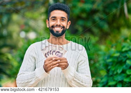 Young african american man smiling happy holding mexican 500 pesos banknotes at the park.