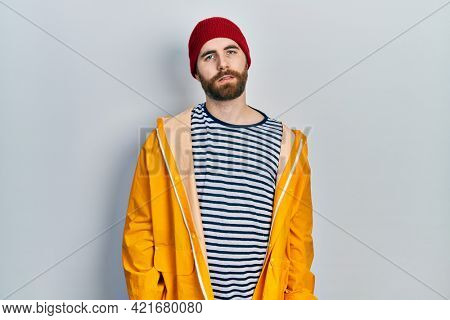 Caucasian man with beard wearing yellow raincoat looking sleepy and tired, exhausted for fatigue and hangover, lazy eyes in the morning.