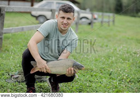 Happy Angler Holds Trophy Carp. Man With Carp Fish. Outdoors Activities, Fishing, Catching Fish Conc