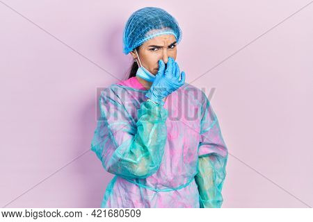 Young brunette woman wearing surgeon uniform and medical mask smelling something stinky and disgusting, intolerable smell, holding breath with fingers on nose. bad smell