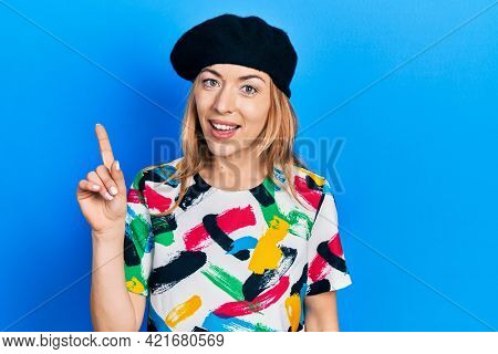 Young caucasian woman wearing french look with beret smiling with an idea or question pointing finger up with happy face, number one