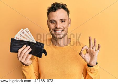 Young hispanic man holding wallet with united kingdom pounds doing ok sign with fingers, smiling friendly gesturing excellent symbol