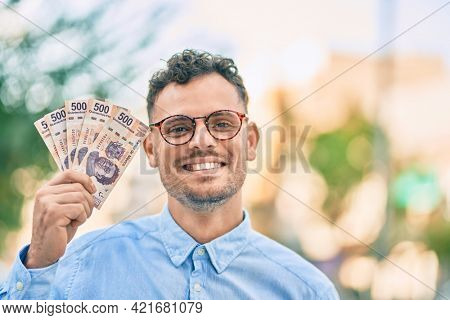 Young hispanic businessman smiling happy holding mexican 500 pesos banknotes at the city.