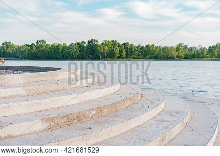 Concrete Round Steps Going To The Water. River. Lake. Sea. Recreation. Water. Nature. Trees. Green.
