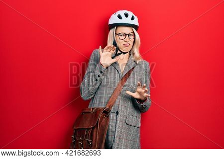 Beautiful caucasian blonde business woman wearing bike helmet disgusted expression, displeased and fearful doing disgust face because aversion reaction. with hands raised