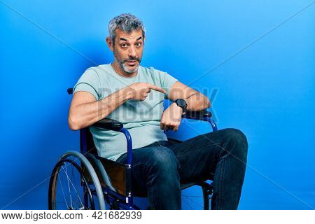 Handsome middle age man with grey hair sitting on wheelchair in hurry pointing to watch time, impatience, upset and angry for deadline delay