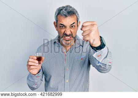 Handsome middle age man with grey hair drinking whiskey shot annoyed and frustrated shouting with anger, yelling crazy with anger and hand raised
