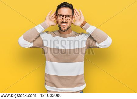 Handsome man with beard wearing casual clothes and glasses trying to hear both hands on ear gesture, curious for gossip. hearing problem, deaf
