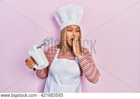 Beautiful hispanic woman holding pastry blender electric mixer bored yawning tired covering mouth with hand. restless and sleepiness.