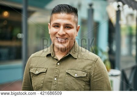 Young latin man smiling happy standing at the city.