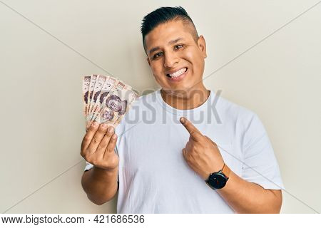 Young latin man holding 500 mexican pesos banknotes smiling happy pointing with hand and finger