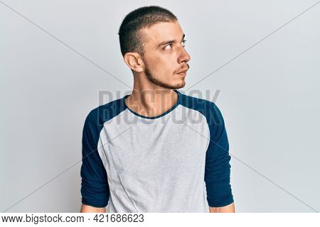 Hispanic young man wearing casual clothes smiling looking to the side and staring away thinking.