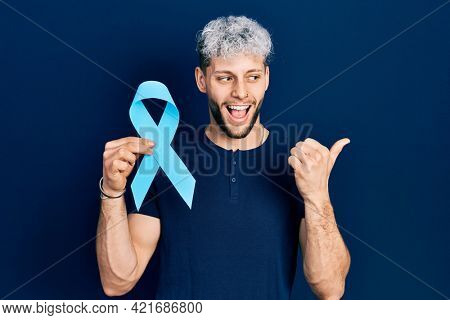 Young hispanic man with modern dyed hair holding pink cancer ribbon pointing thumb up to the side smiling happy with open mouth