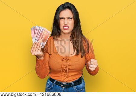 Beautiful hispanic woman holding norwegian krone banknotes annoyed and frustrated shouting with anger, yelling crazy with anger and hand raised