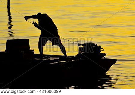 Silhouette Of A Fishermen With Outboard Motor Boat Ready To Fishing During Beautiful Sunrise At Labu